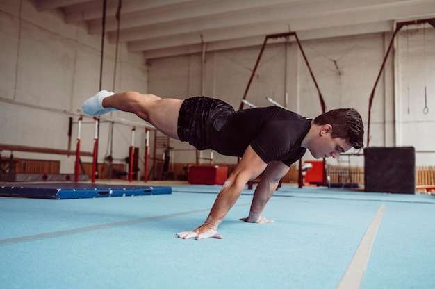 Hombre de vista lateral entrenando con barras paralelas