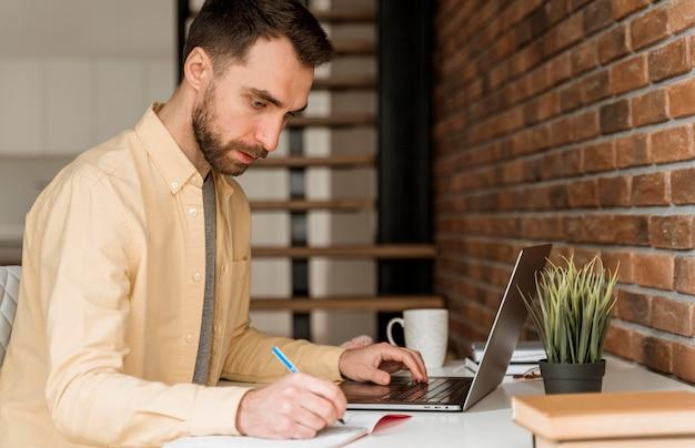 Hombre de vista lateral con videollamada en la computadora portátil y escribiendo