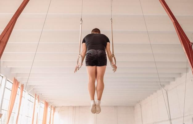 Hombre de vista posterior entrenando en anillos de gimnasia