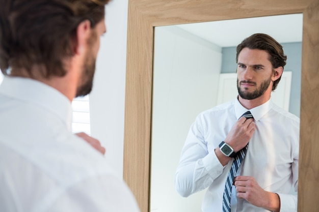 Hombre vistiéndose en el dormitorio mientras mira al espejo