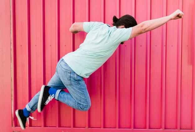 Hombre volando con los brazos levantados contra la pared de color rosa corrugado
