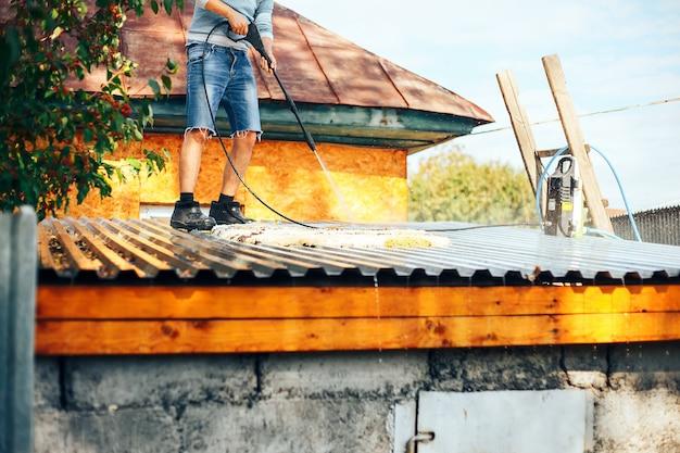 Hombre wach limpiar la alfombra al aire libre en el techo con agua