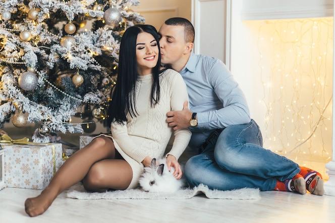 Hombre y mujer bonita con un pequeño conejo posan ante un brillante árbol de navidad