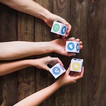 Hombre y mujer sosteniendo bloques de iconos de redes sociales en la mesa de madera