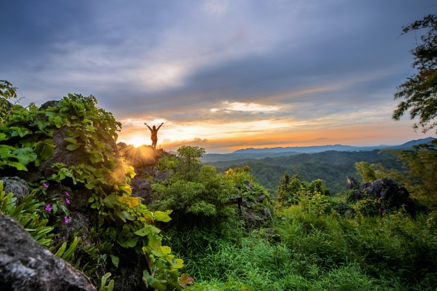Hombre y puesta de sol en alta montaña