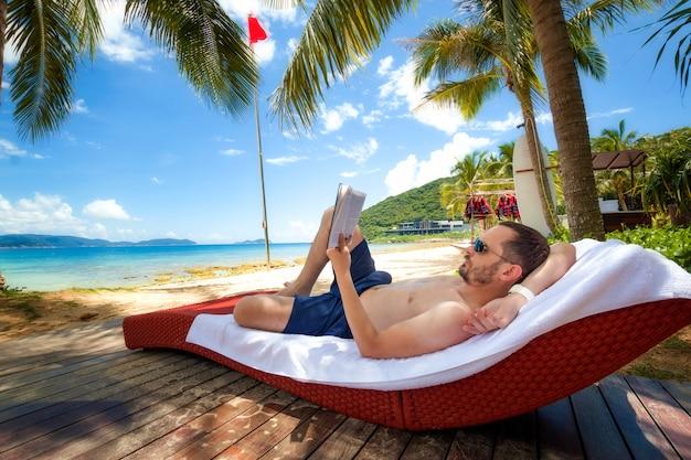 El hombre yace en la playa, lee un libro y toma el sol