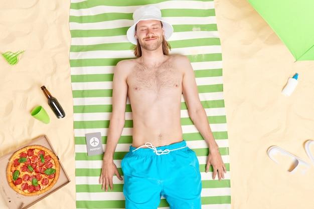 El hombre yace sobre una toalla en la playa disfruta de tiempo de recreación posa con los ojos cerrados a la orilla del mar rodeado por una deliciosa pizza botella de protector solar de abeja zapatillas sombrilla