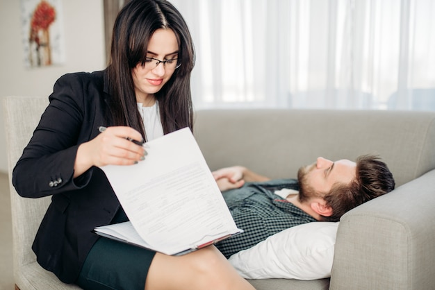 El hombre yace en el sofá en la recepción del psicoterapeuta