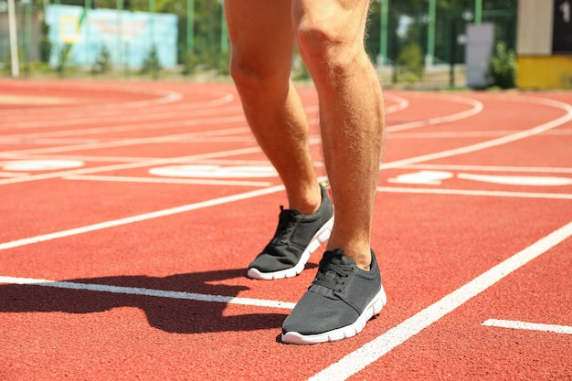 Hombre en zapatillas de deporte en la pista de atletismo roja, cerrar