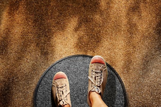 Hombre en los zapatos de la zapatilla de deporte pasos sobre la línea del círculo hasta el límite exterior