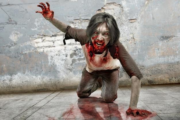 Hombre zombie enojado con la boca sangrienta gateando