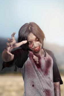 Hombre zombie espeluznante con manos arañando de pie al aire libre