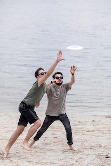 Hombres adultos corriendo en la playa para atrapar el frisbee