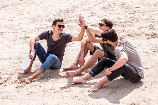 Hombres adultos dando alta cinco el uno al otro