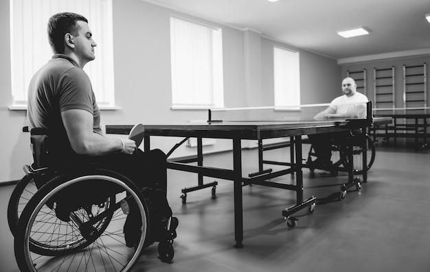 Hombres adultos discapacitados en silla de ruedas jugando al tenis de mesa