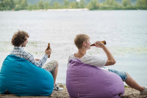 Hombres adultos relajantes con cerveza cerca del agua