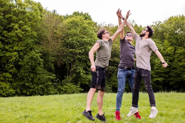 Hombres adultos saltando y dando alta cinco.