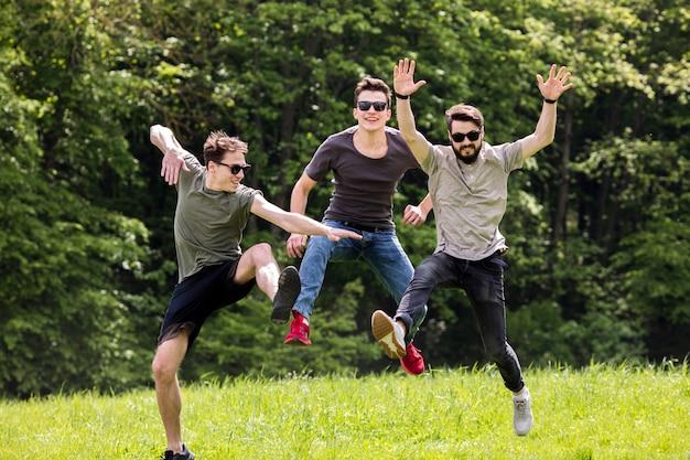 Hombres adultos saltando en la naturaleza y posando en el aire.
