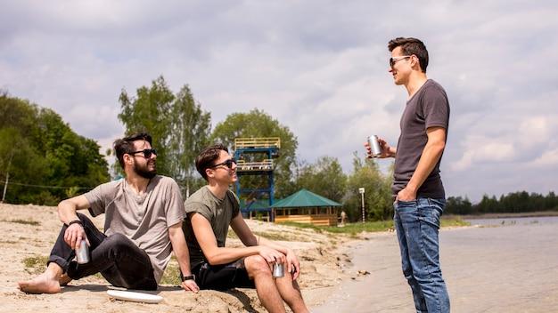 Hombres adultos sentados en la playa y escuchando a un amigo