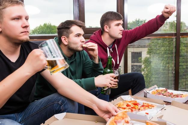 Hombres aficionados viendo fútbol en la televisión y bebiendo cerveza. tres hombres bebiendo cerveza y divirtiéndose juntos en el bar.