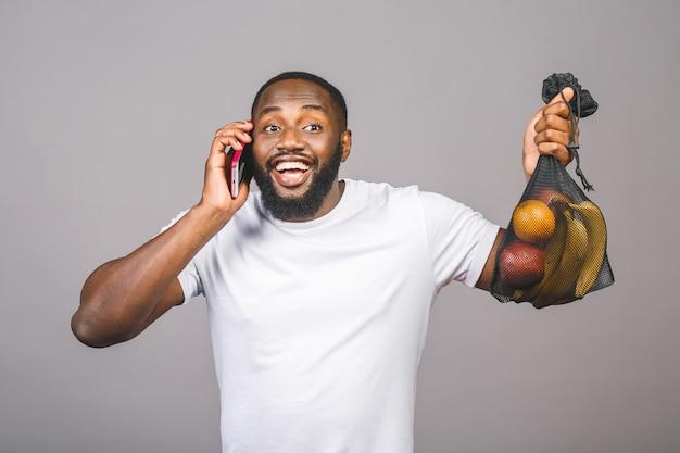 Los hombres afroamericanos negros está sosteniendo una bolsa de malla con productos sin paquete de plástico aislado sobre fondo gris. usando el teléfono.