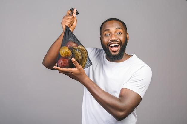 Los hombres afroamericanos negros está sosteniendo una bolsa de malla con productos sin paquete de plástico aislado sobre fondo gris.
