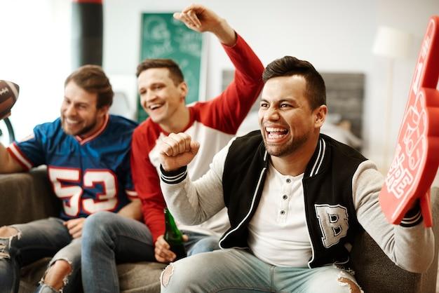 Hombres alegres apoyando a su equipo deportivo