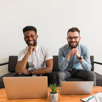 Hombres alegres cerca de computadoras portátiles