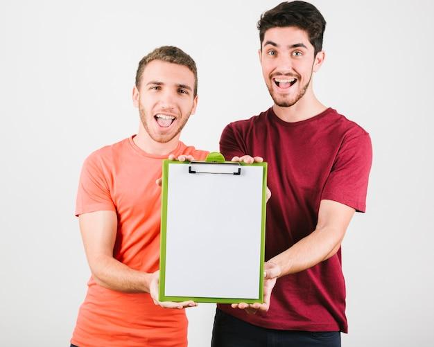 Hombres alegres mostrando tableta con papel a cámara