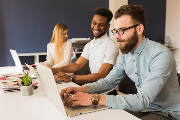Hombres alegres que usan computadoras portátiles