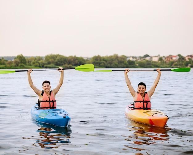 Hombres alegres sosteniendo kayak remo sobre la cabeza disfrutando del kayak