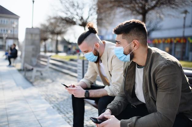 Hombres amigos al aire libre en la calle de la ciudad con un teléfono inteligente, un coronavirus y un nuevo concepto normal.
