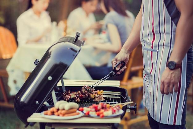 Los hombres asiáticos están cocinando para un grupo de amigos para comer barbacoa