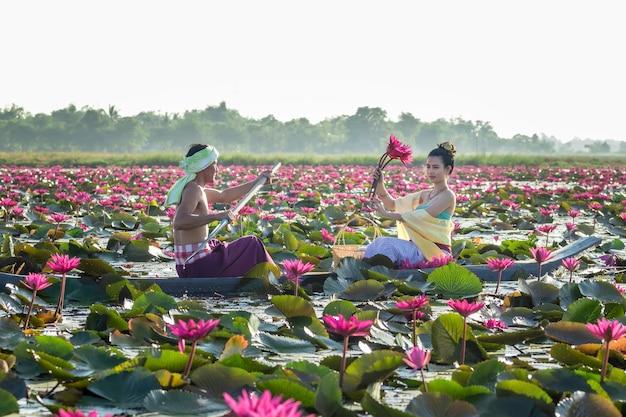 Hombres asiáticos están recogiendo flores de loto rojas para que las mujeres asiáticas adoren