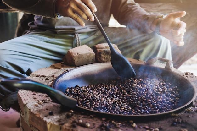 Hombres asiáticos están sentados tostando granos de café en una sartén en una estufa antigua