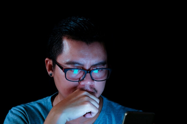 Los hombres asiáticos están usando el teléfono o la tableta con una luz azul en la oscuridad, efectos conceptuales de la tecnología.