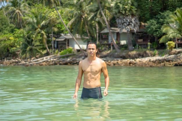 Hombres asiáticos que nadan en las rocas y los árboles del fondo del mar en koh phangan, surat thani.