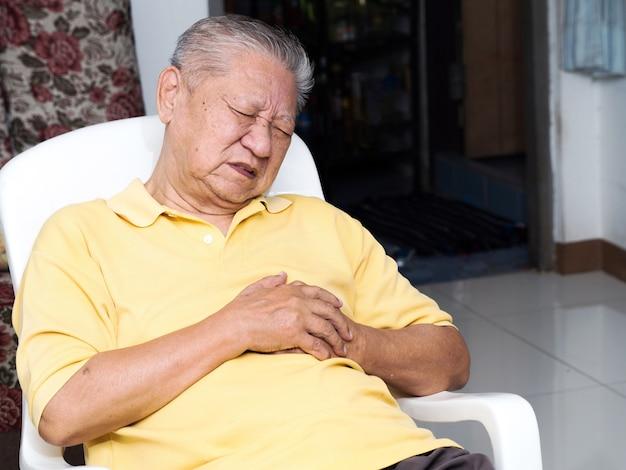 Hombres asiáticos seniles que se sientan en una silla en la sala de estar con ataques cardíacos.