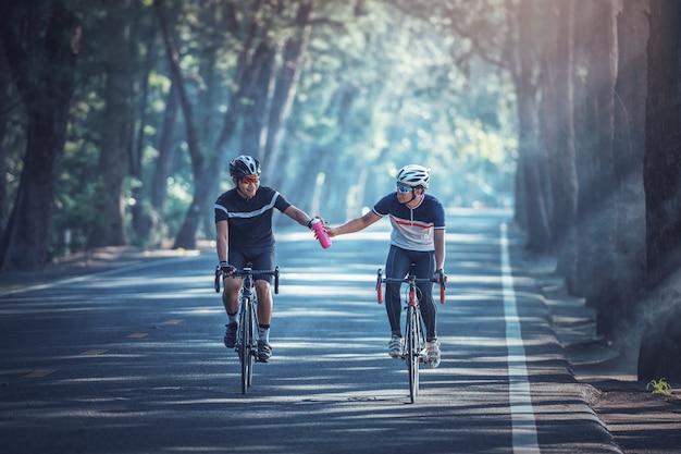 Los hombres asiáticos van en bicicleta por la mañana y comparten agua entre ellos.