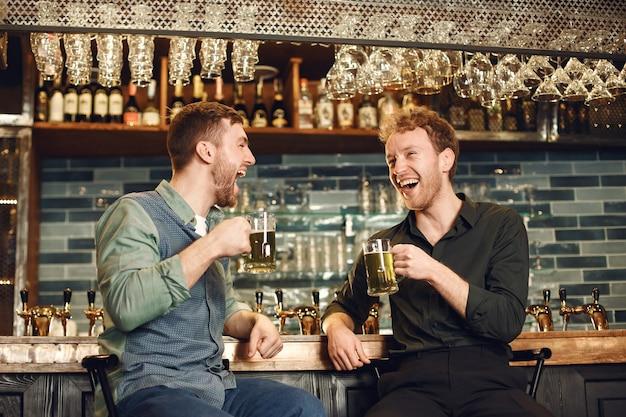 Hombres en el bar. chicos bebiendo cerveza. los hombres se comunican con una jarra de cerveza.
