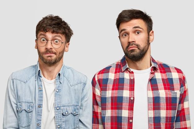 Hombres barbudos desconcertados con expresión desorientada, no saben cómo hacer que el proyecto funcione y por qué empezar, tienen miradas desconcertadas, se sienten desconcertados, aislados sobre una pared blanca