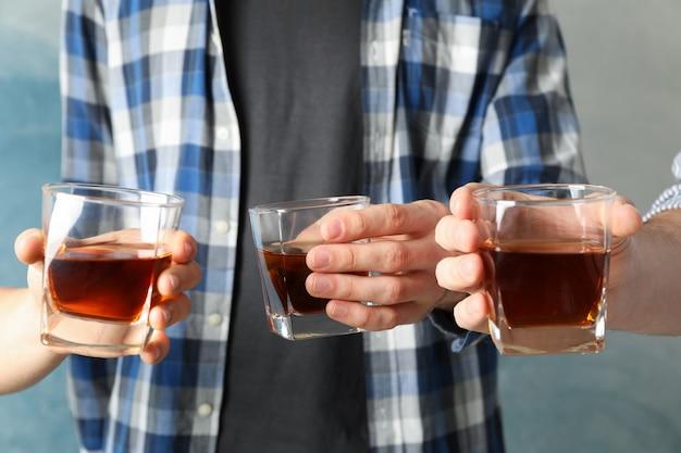 Los hombres beben, aplausos. vasos de whisky contra azul