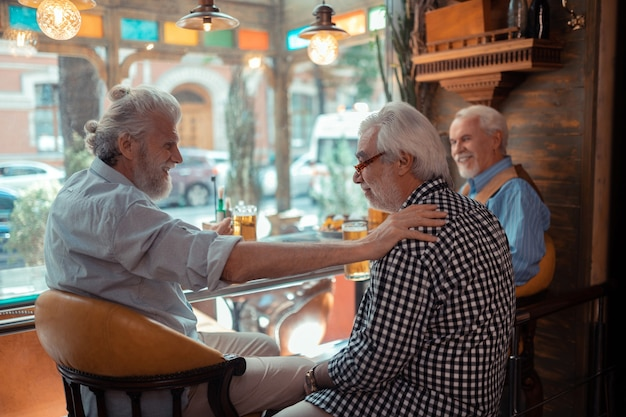 Hombres bebiendo cerveza. tres hombres jubilados que se sienten bien mientras se relajan en un pub mientras beben cerveza