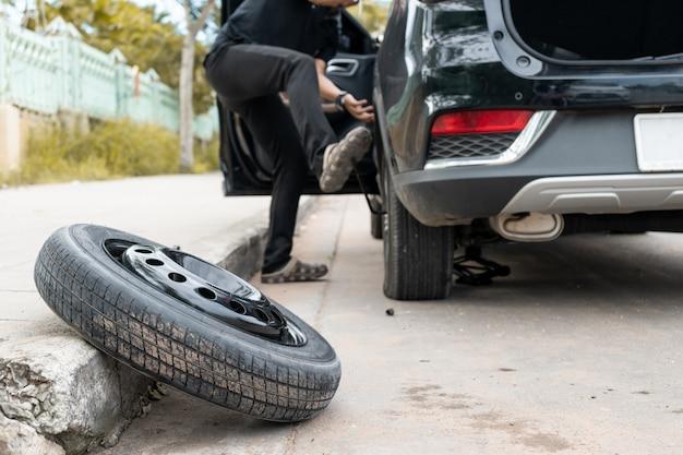 Hombres está cambiando los neumáticos en el lado de la carretera