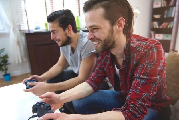 Hombres cariñosos jugando playstation en la sala de estar