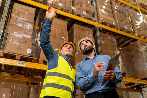 Hombres con casco trabajando en almacén