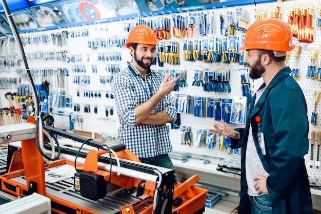 Los hombres con cascos protectores seleccionan herramientas.