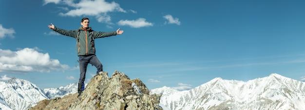 Los hombres celebran el éxito extendiendo sus brazos, montañas nevadas. logro de sus metas.