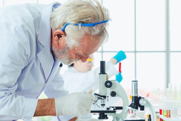 Hombres de ciencia trabajando con microscopios químicos en laboratorio