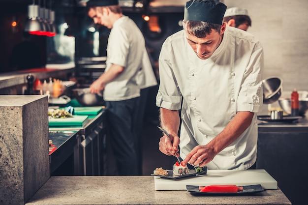 Hombres cocineros preparando sushi